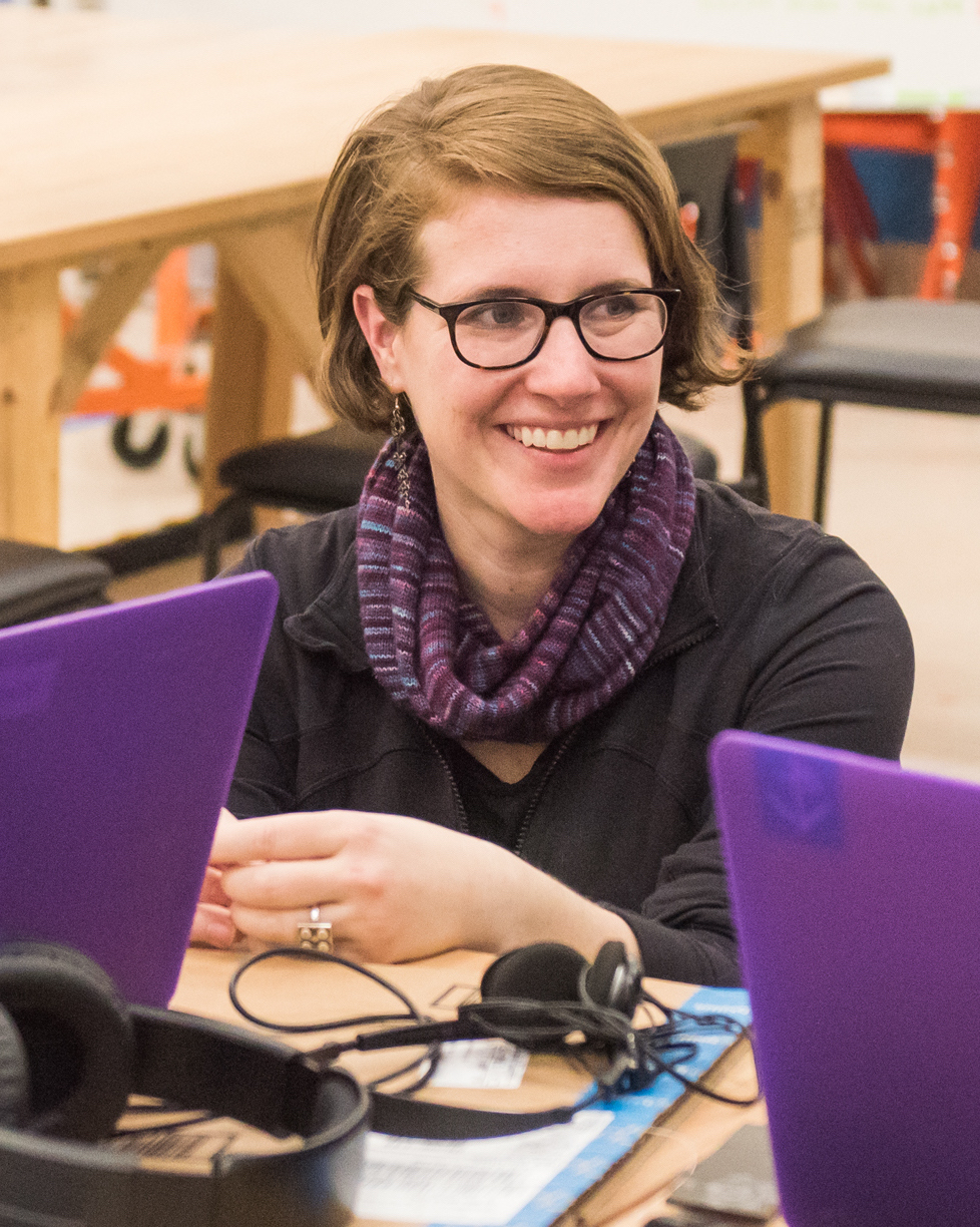 Amy Hurst smiling and sitting between two purple laptops